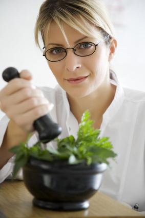 kvinne knuser urter i en morter