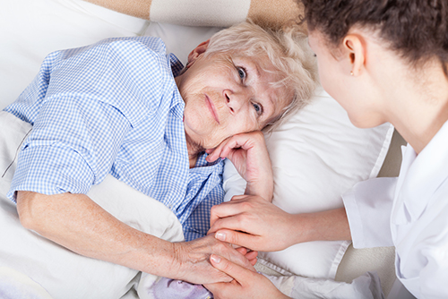 Dame sengeliggende pasient med lege som holder pasientens hender