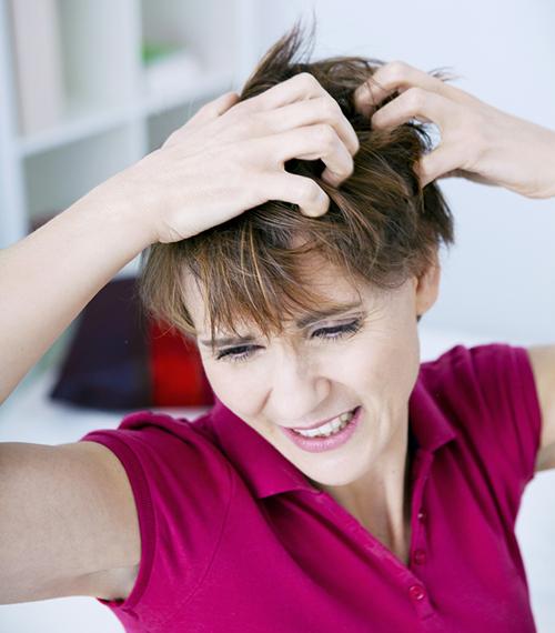 Dame som klør seg intest i håret