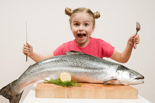 Jente med kniv og gaffel over en kjempestor fisk