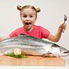 Jente med kniv og gaffel over en veldig stor fisk