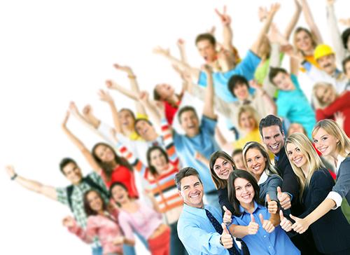 Stor gruppe glade mennesker med hendene i været og noen i front som viser tommelen opp
