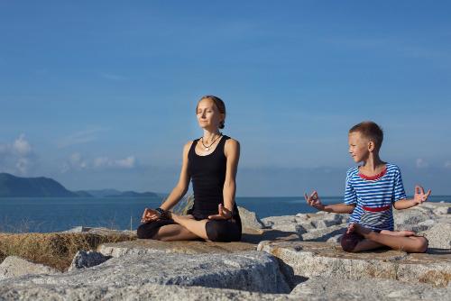 Kvinne og gutt sitter ute og mediterer