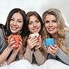 tre kvinner med kaffekopper