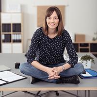 Kvinne som sitter på et kontorbord med korslagte ben