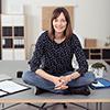 kvinne som sitter på bordet med korslagte ben