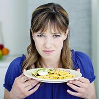 Bekymret dame med en tallerken mat
