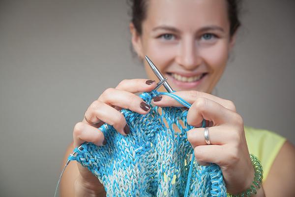 Dame som viser sitt strikketøy