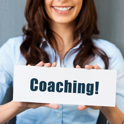 Kvinne holder skilt med tema coaching