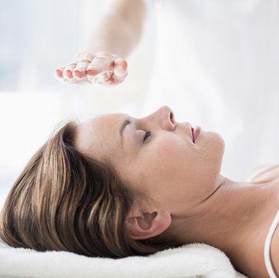 Dame ligger og får healing med healerens hånd over kroppen