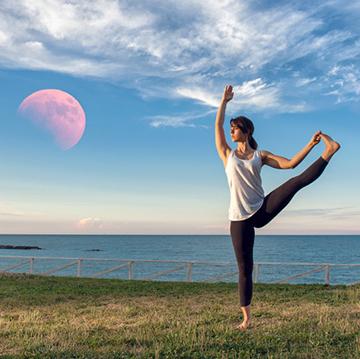 Dame som praktiserer yoga med rød måne i bakgrunnen