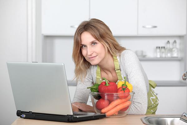 Kvinne med pc og en glassbolle med grønnsaker
