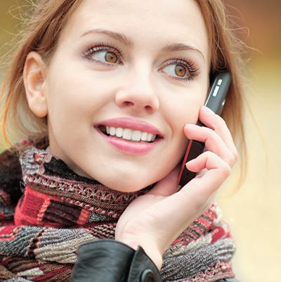 Kvinne som holder telefon inntil øret.