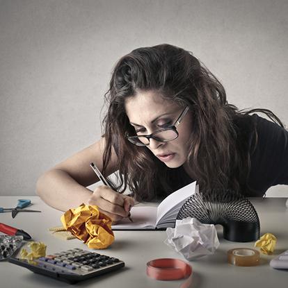 Dame sitter ved kontorpult og ser ut til å ha for mange oppgaver å følge opp
