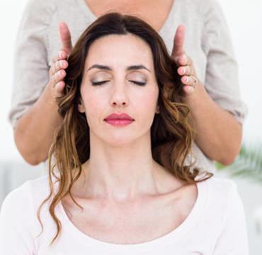 Dame som mottar healing fra hender på hver side av hodet
