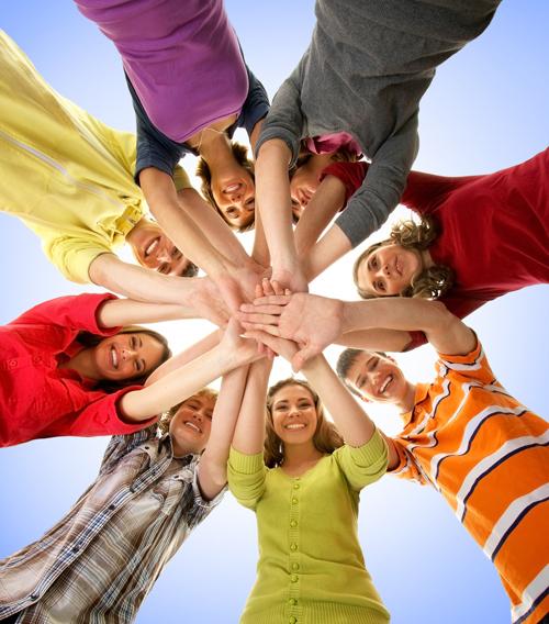 mange mennesker i sirkel som strekker hendene inn mot midten