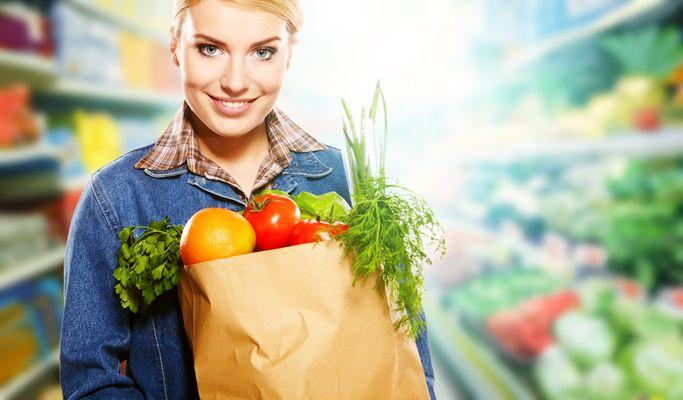 Dame med papirpose full av grønnsaker