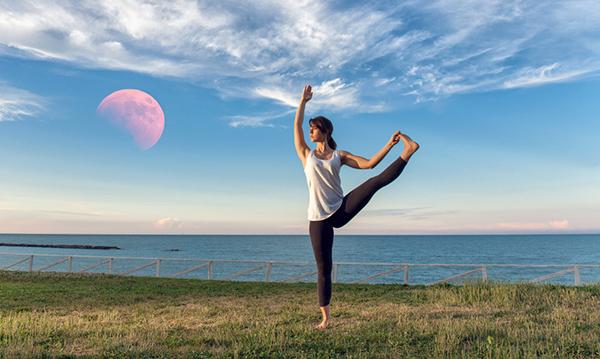 Dame praktiserer yoga med rød måne i bakgrunnen